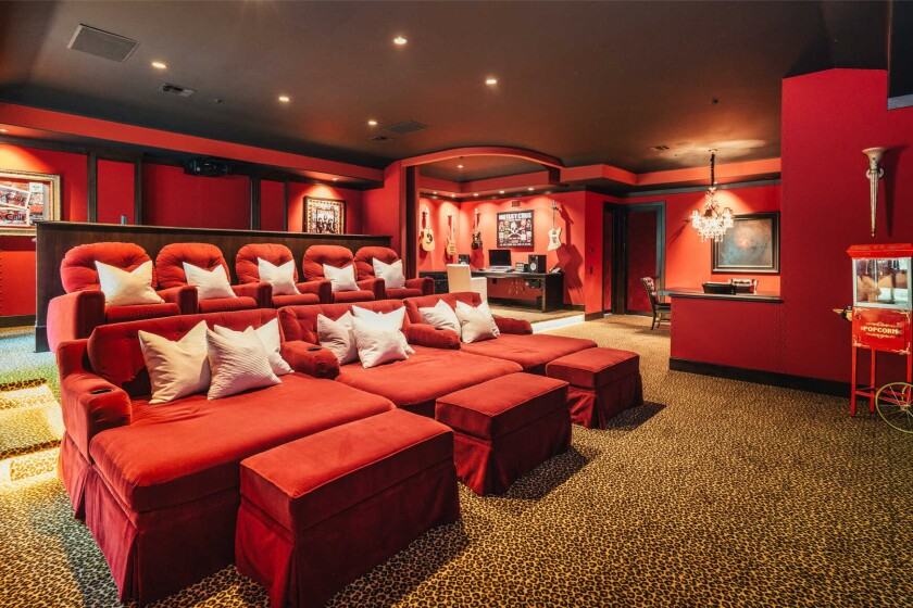 The custom home includes a library, billiards room and crimson-colored movie theater with cheetah-print carpet.