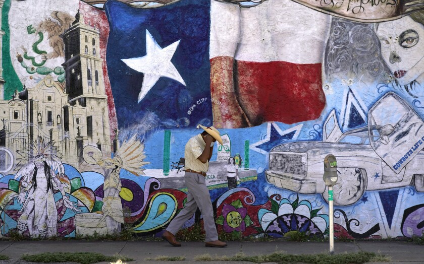 A man adjusts his face mask as he walks past a mural in the heavily Latino section of Oak Cliff in Dallas, Wednesday, Sept. 22, 2021. Texas this week will begin redrawing congressional lines, and Latino advocates and officeholders say it's time to correct past wrongs. The state's explosive population growth over the past decade, half of which comes from Latinos, has earned it two new congressional seats. At least one should be a Latino-majority congressional seat in the Dallas area, they argue. (AP Photo/LM Otero)