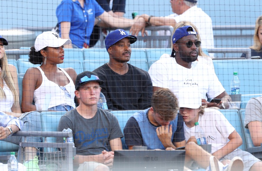 Former NBA star Dwyane Wade, right, attends a Dodgers game Aug. 25 along with his wife, actress Gabrielle Union, and interior designer Adair Curtis.