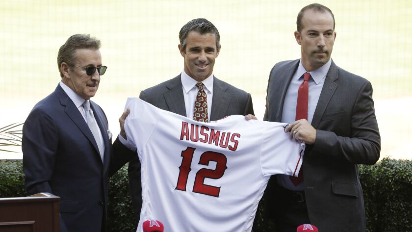 ANAHEIM, CA -- OCTOBER 22, 2018: Brad Ausmus, flanked by Angels owner Arte Moreno, left, and General