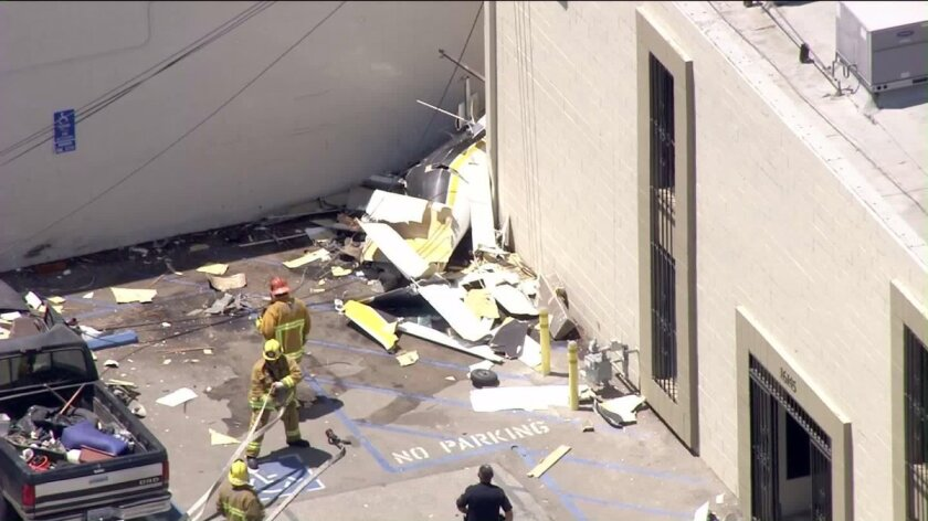 A small plane crashed into the side of a building near the Van Nuys Airport, fire officials said.