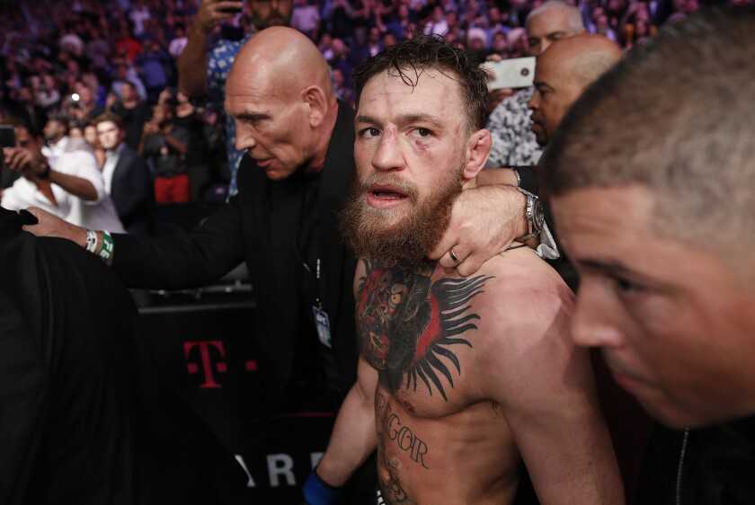 Conor McGregor is escorted from the cage area after fighting Khabib Nurmagomedov in a lightweight title mixed martial arts bout at UFC 229 in Las Vegas, Saturday, Oct. 6, 2018. Nurmagomedov won the fight by submission during the fourth round to retain the title.