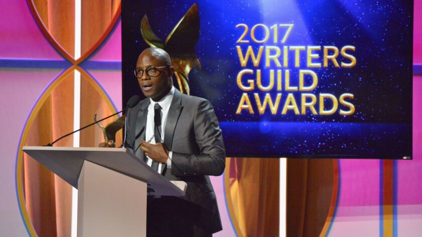 """Director Barry Jenkins accepts the original screenplay award for """"Moonlight"""" during the 2017 Writers Guild Awards ceremony."""