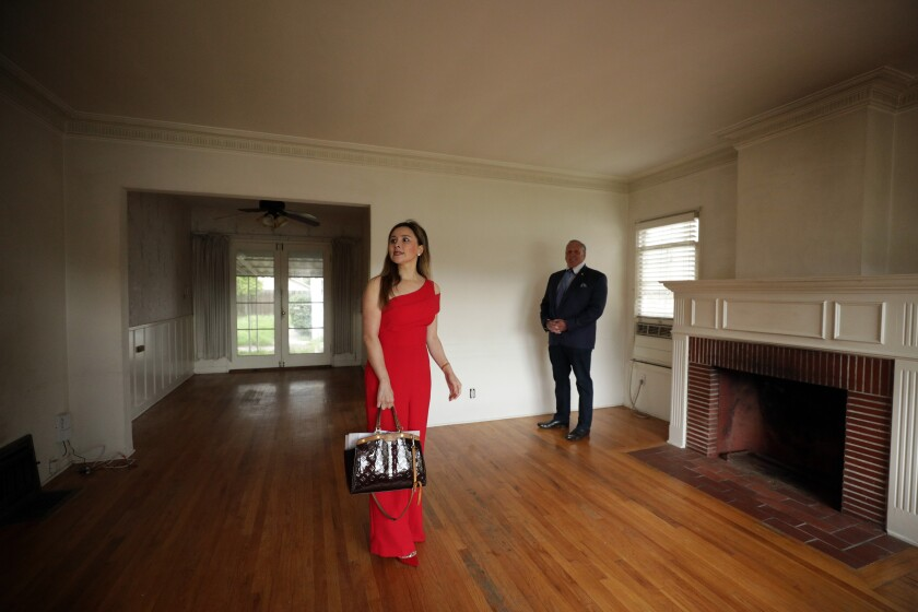 Real estate investor Celine Yan and her agent, Jeff Brager, look over a North Hollywood house she is purchasing.