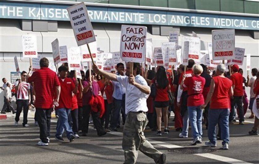 Kaiser Permanente employees walkout to protest proposed benefit cuts and a lack of progress on contract talks outside the Kaiser Permanente hospital Wednesday, Sept. 21, 2011, in Los Angeles. About 2,500 employees: nurses, social workers and therapists walked the picket Wednesday as part of a large