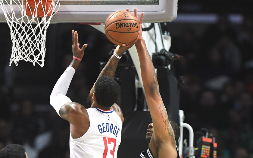 Clippers forward Paul George tries to put up a shot over Spurs forward LaMarcus Aldridge during the second quarter of the Clippers' 108-105 win Monday at Staples Center.