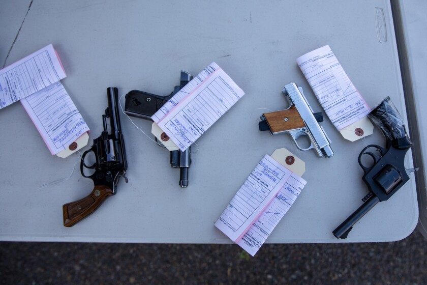 Guns that will later be destroyed sit on a table during a gun buyback exchange at Encanto Southern Baptist Church