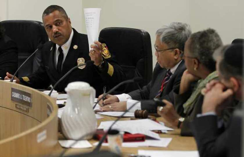 L.A. Fire Chief Brian Cummings left, talks to members of the city Fire Commission about 911 response times at a meeting in March.