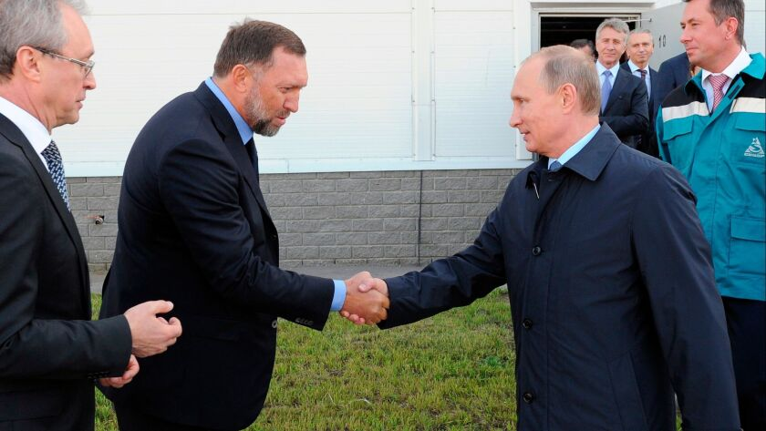 In this 2014 photo, Russian President Vladimir Putin, right, shakes hands with Russian metals magnate Oleg Deripaska while visiting the RusVinyl plant in Kstovo, in Russia's Nizhny Novgorod region.