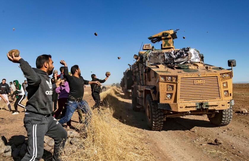 Kurdish demonstrators hurl rocks at a Turkish military vehicle on Nov. 8