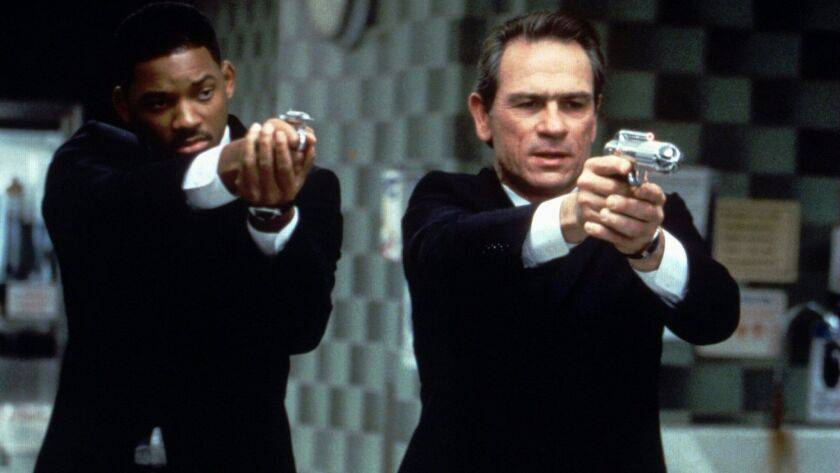 69743 (BC-BPI-MENINBLACK) Tommy Lee Jones, r., and Will Smith are the Men in Black, providers of int