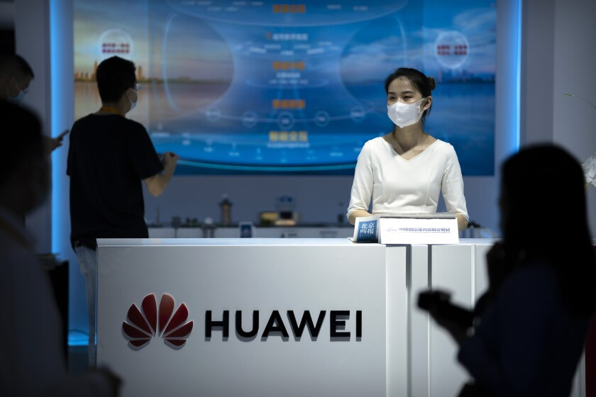 Una empleada atiende un stand de la firma china Huawei durante la Feria Internacional de Comercio de Servicios de China (CIFTIS) en Beijing, el viernes 3 de septiembre de 2021. (AP Foto/Mark Schiefelbein)