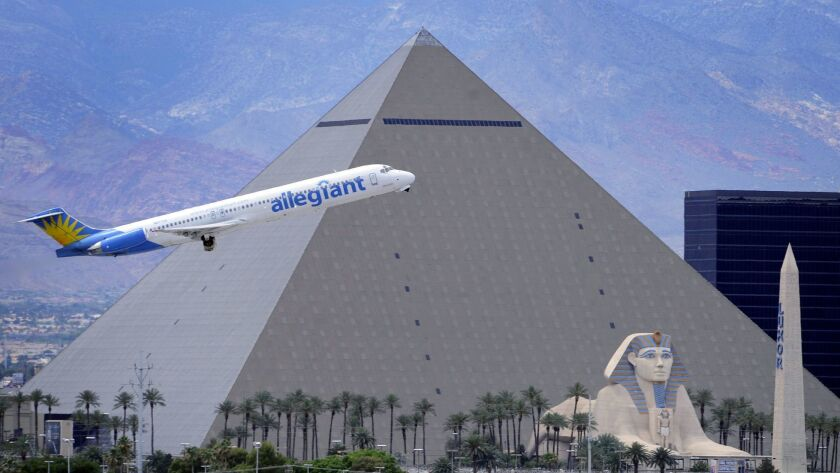 In this Thursday, May 9, 2013, photo, An Allegiant Air jetliner flies by the Luxor Resort & Casino a