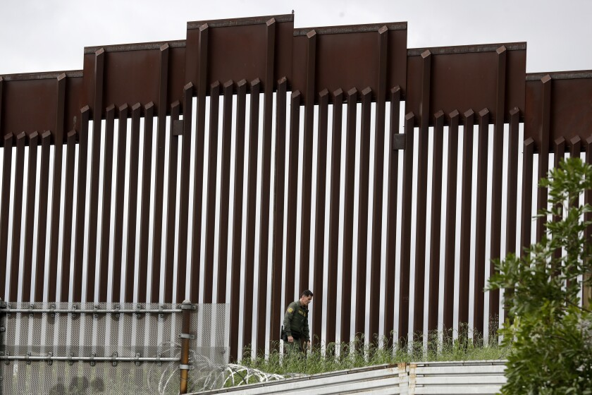 Un agente de la Patrulla Fronteriza estadounidense camina junto al muro fronterizo que separa Tijuana, México, de San Diego.