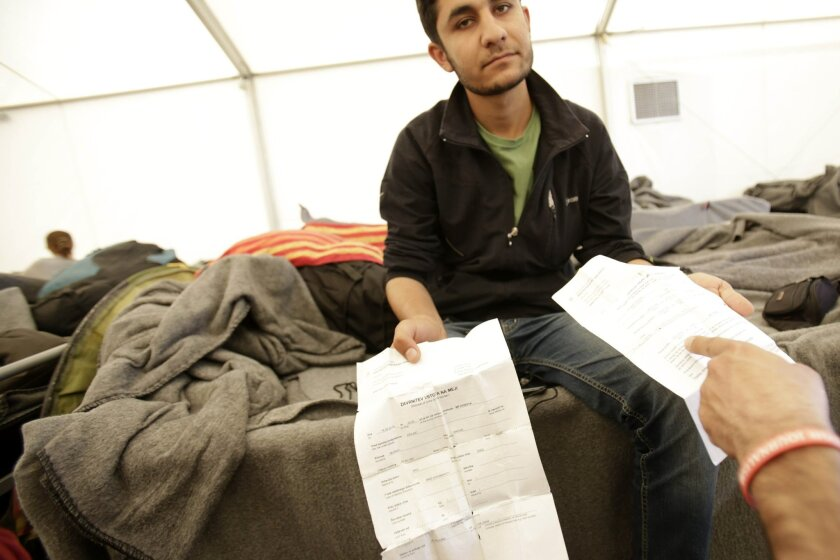In this photo taken on Saturday, April 16, 2016 at the Greek-Macedonian border near the northern Greek village of Idomeni, Iraqi migrant Anwar Ismail Murad, shows papers from Slovenian authorities from where he was expelled. Stranded refugees tell of being pushed back into Greece despite having made it further north through the Balkans when the borders were still open. (AP Photo/Amel Emric)