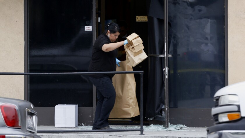 Los Angeles County Sheriff Department Crime Lab investigators gather bags of evidence at a pot dispensary in Walnut Park where one of the store owners shot and critically wounded two men attempting to rob the store.