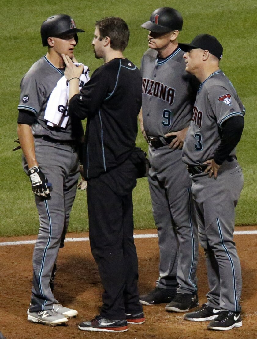 Arizona Diamondbacks' Nick Ahmed , left, is checked by a team trainer as third base coach Matt Williams, (9) and manager Chip Hale (3) look on after being hit by a pitch from Pittsburgh Pirates relief pitcher Arquimedes Caminero in the eighth inning of a baseball game in Pittsburgh, Tuesday, May 24