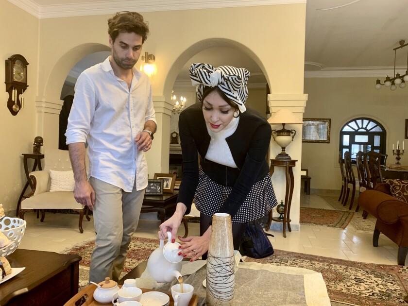 Amin Sirati ( R ) and his wife Shamim Darchini (L) pour tea at Sirati's house in the Iranian city of