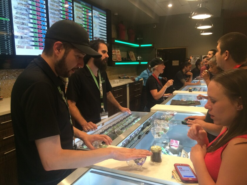 Employees at Las Vegas ReLeaf help customers select marijuana products early Saturday,the first day pot sales for recreational use became legal.