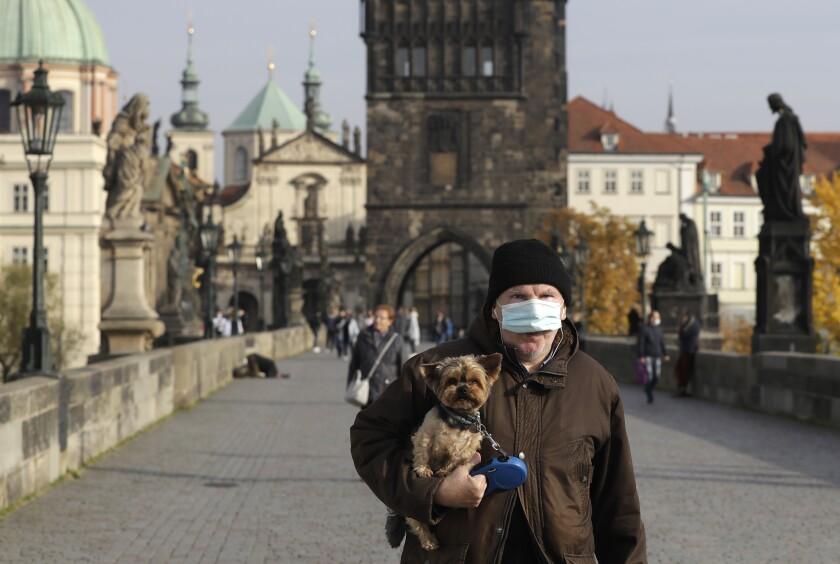 Un hombre camina con su perro en Praga en la República Checa el 21 de octubre del 2020. (AP Photo/Petr David Josek)