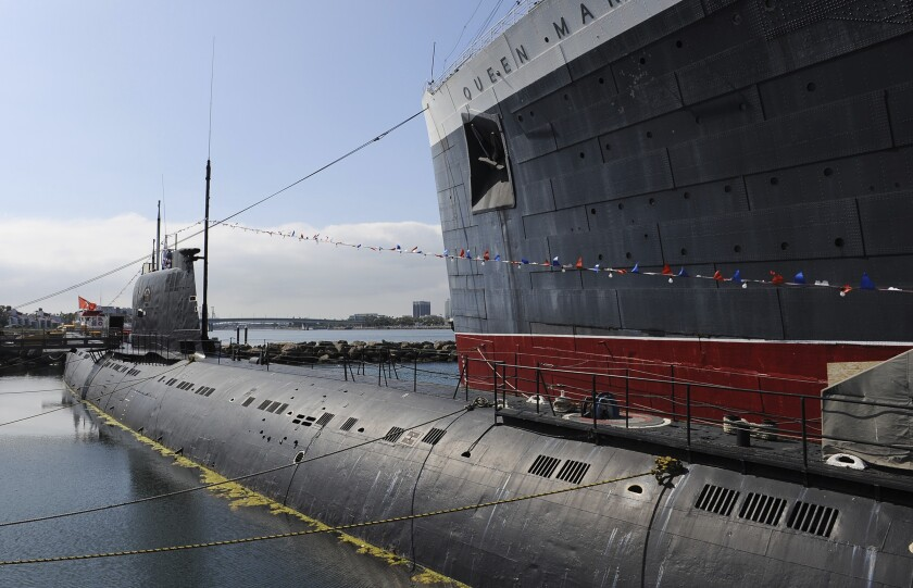 The Russian Foxtrot-Class submarine known as the Scorpion sits next to the Queen Mary.