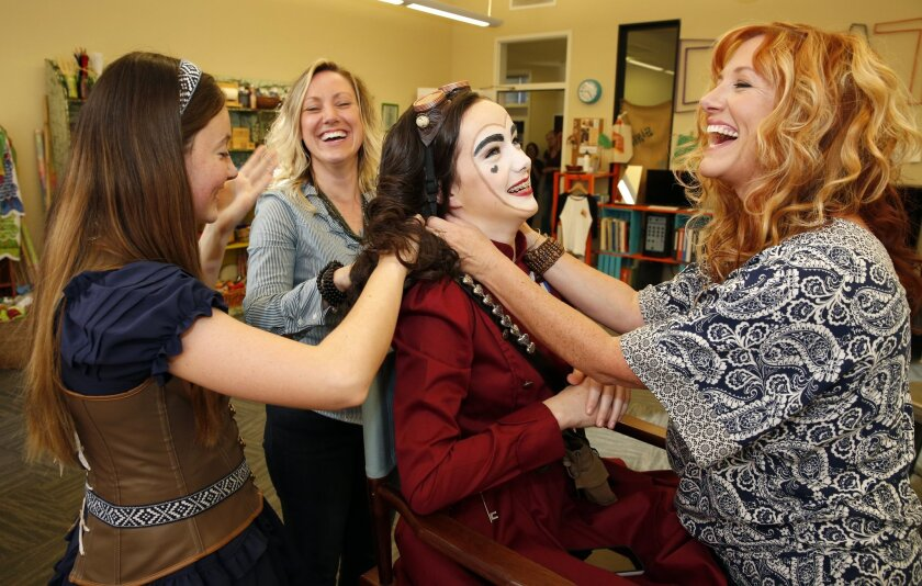 """Kaitlyn O'Leary (red jacket) (left to right) Emma Rasse, Courtney Corey and Marci Wuebben work on """"The Queen of Hearts"""" production."""