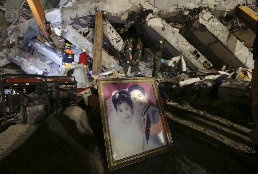 A recovered wedding portrait is propped up at the search and rescue staging area of a collapsed building complex in Tainan, Taiwan, Monday, Feb. 8, 2016.  More than 100 people are believed to still be under the debris in a powerful quake that struck on Saturday, Feb. 6, during the most important fa