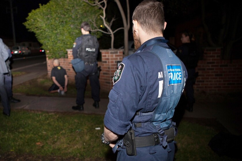 Australian Federal Police officers detain a suspect in Sydney after Australia's largest-ever counterterrorism raids.