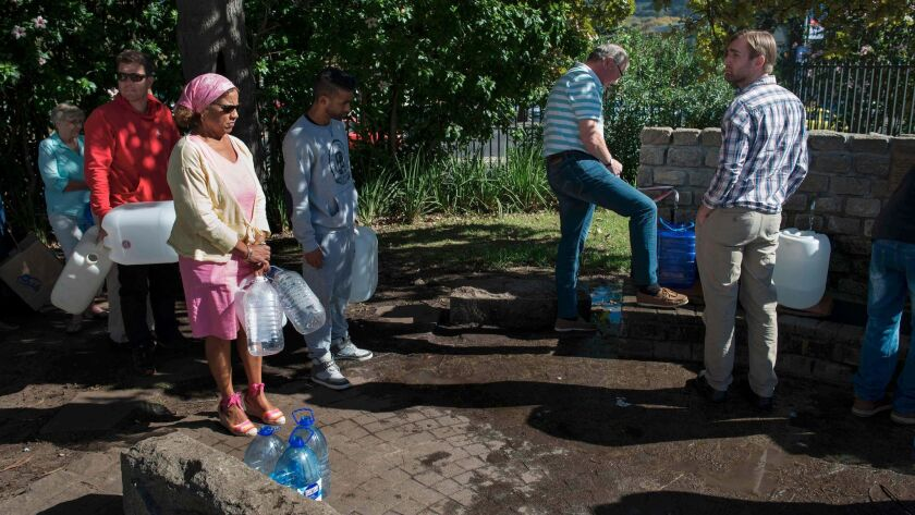 People line up on May 15 to collect drinking water from taps that are fed by a spring in Cape Town.
