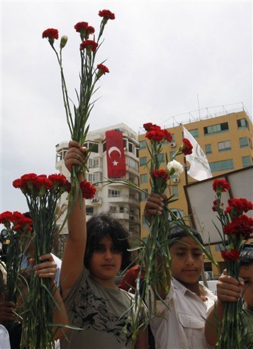 Palestinian children hold up red and white carnations during a protest against the Israeli naval commando raid on a flotilla attempting to break the blockade on Gaza, at the port in Gaza City, Tuesday, June 1, 2010. Palestinians in Gaza declared a general strike and a day of wrath following Israel'