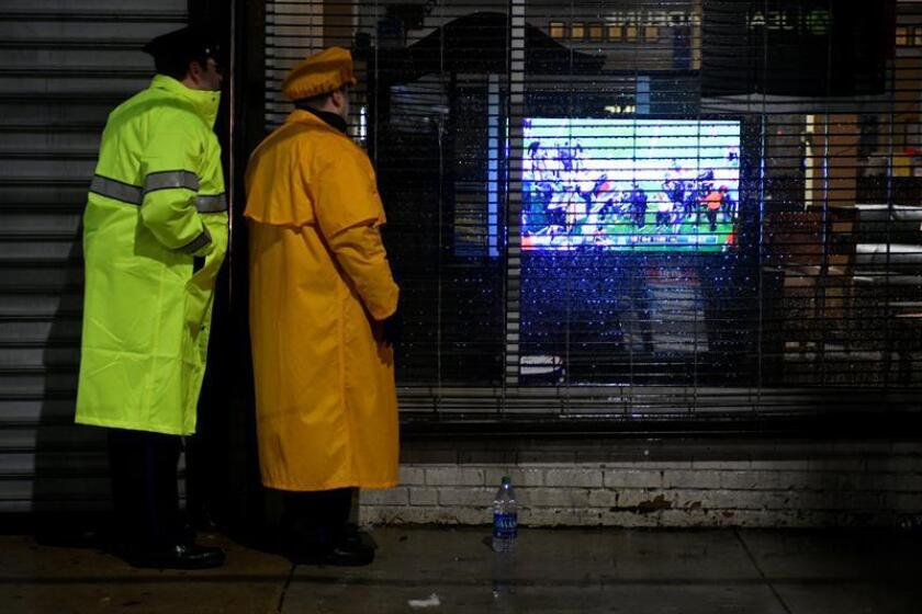Dos policías ven el partido del Super Bowl a través del cristal de un comercio, ayer en Filadelfia. EFE