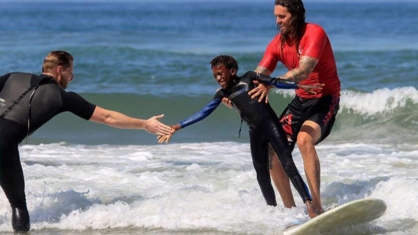 Thomas Dorsey, 10, who is visually impaired, is congratulated Sunday during a surfing event for the blind and visually impaired sponsored by the Swamis Surfing Association at South Carlsbad State Beach where he tandem surfed with Matt Allen.