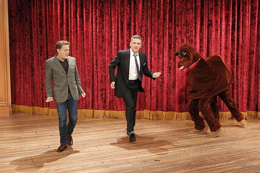 "Craig Ferguson, center, with comic Eddie Izzard, dances with Secretariat on CBS' ""The Late Late Show."" Ferguson will leave in December."