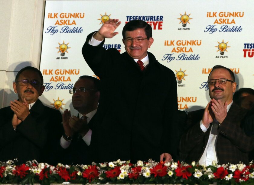 Turkish Prime Minister Ahmet Davutoglu salutes supporters gathered outside ruling Justice and Development Party headquarters in Ankara, Turkey, Sunday, Nov. 1, 2015. Turkey's ruling party appeared to sweep back into single-party rule after a stunning victory in Sunday's parliamentary election, and