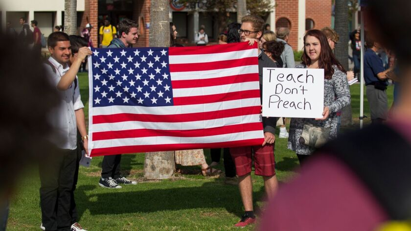 Members of the Republican Club at Orange Coast College including Brittany Perrigo, right, hold a cou
