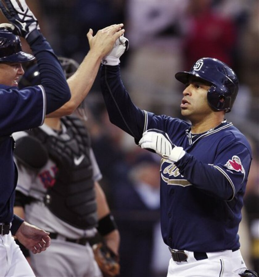 San Diego Padres' Jerry Hairston Jr., right, is congratulated by teammates after hitting a grand slam off New York Mets pitcher Hisanori Takahashi during the second inning of a baseball game Monday, May 31, 2010, in San Diego. (AP Photo/Denis Poroy)