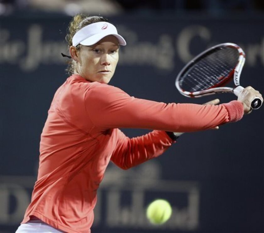 Samantha Stosur, of Australia, returns to Eugenie Bouchard, of Canada, at the Family Circle Cup tennis tournament in Charleston, S.C., Thursday, April 4, 2013. Stosur retired in the second set due to an injury. (AP Photo/Mic Smith)
