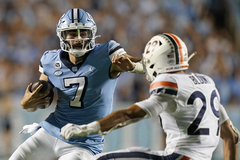 North Carolina quarterback Sam Howell (7) runs the ball as Virginia free safety Joey Blount (29) defends during the second half of an NCAA college football game in Chapel Hill, N.C., Saturday, Sept. 18, 2021. (AP Photo/Gerry Broome)