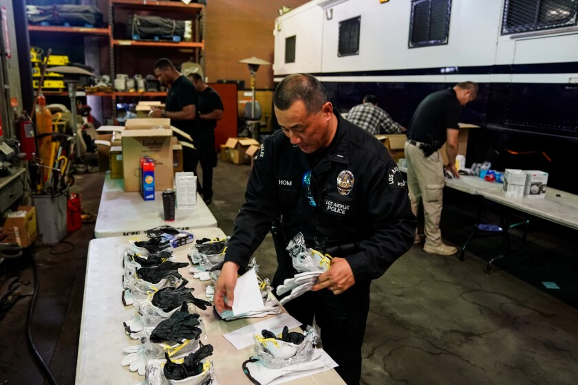 Lt. Jay Hom helps assemble personal safety kits for officers, including a mask and gloves.