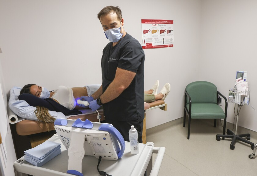 Dr. J. Scott Overcash trains Raquel Taitingfong on using a FibroScan machine.