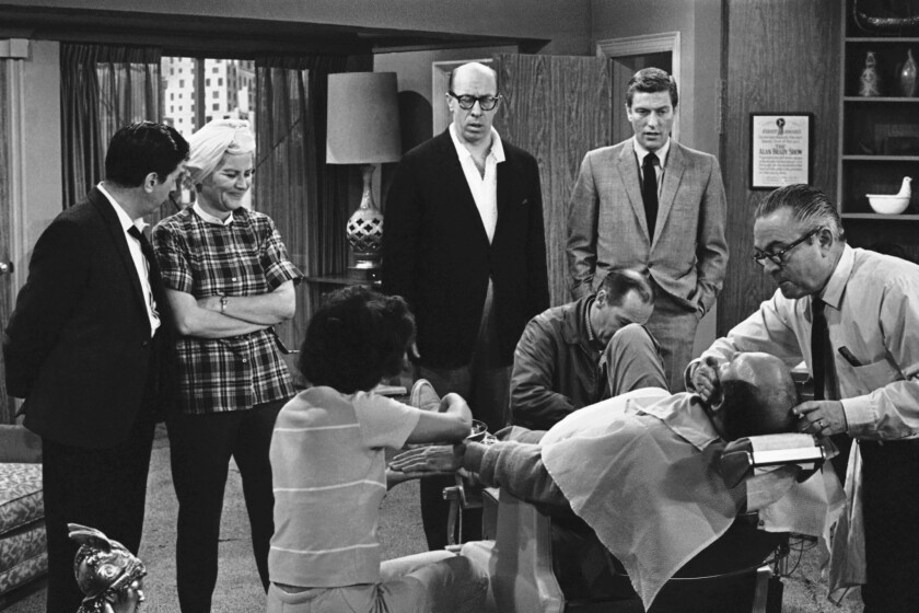 """In this April 11, 1963, photo, standing from left, Morey Amsterdam, Rose Marie, and Richard Deacon, and Dick Van Dyke, right, gather around Carl Reiner, in barber chair during a rehearsal of an episode for the """"The Dick Van Dyke Show."""" Family spokesman Harlan Boll said Marie died Dec. 28, 2017."""