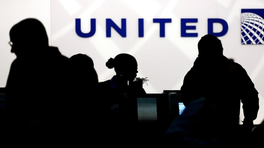 Travelers check in at the United Airlines ticket counter at O'Hare International Airport in Chicago on Dec. 21, 2013.