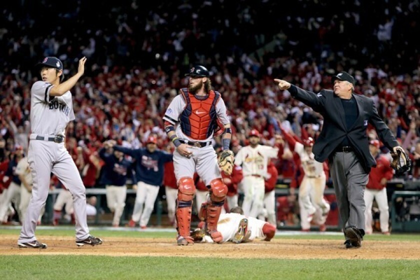 Home plate umpire Dana DeMuth, right, calls St. Louis' Allen Craig safe at home as catcher Jarrod Saltalamacchia, center, and Koji Uehara, left, react in the ninth inning of Game 3 of the World Series.