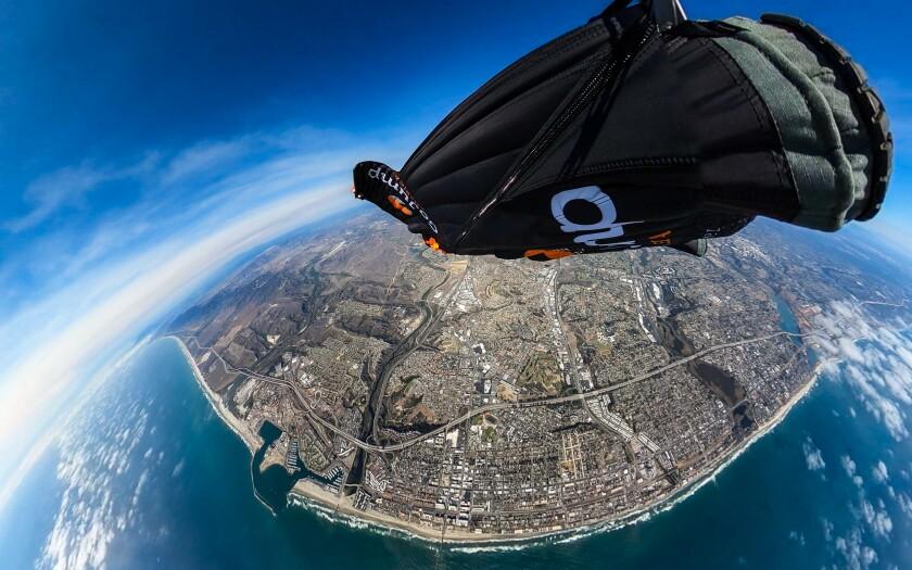 Skydiver Chris Geiler of Oceanside soaring high above Oceanside in his wingsuit.