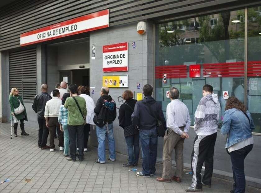 Job-seekers line up outside an employment office in Madrid.