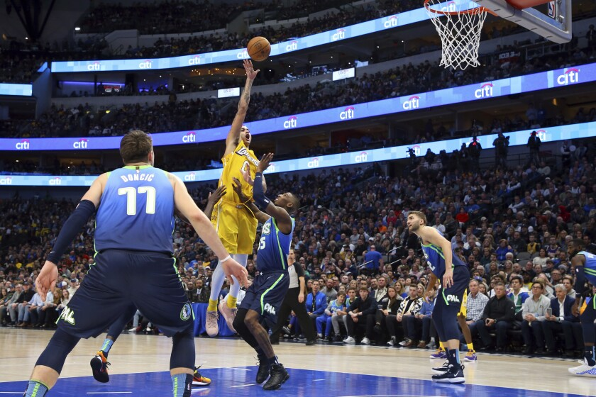 The Lakers' Kyle Kuzma, who scored a season-high 26 points, shoots over the Mavericks' Delon Wright on Jan. 10, 2020.