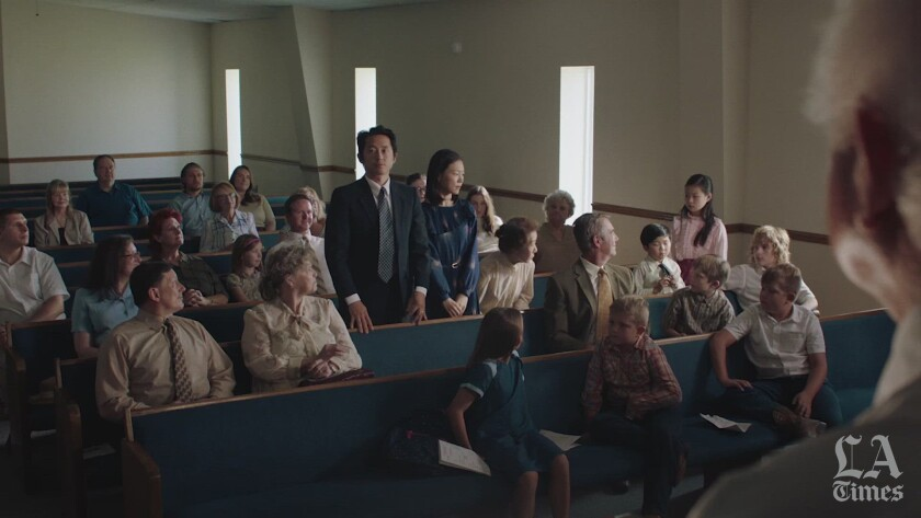 A Korean American family stands while congregants in a mostly white church clap for them