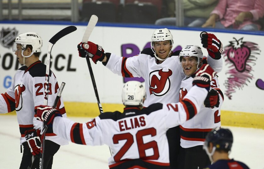 RETRANSMITTING TO CORRECT NAME TO HAVLAT NOT HAVIAT New Jersey Devils players Martin Havlat (9), Mike Cammalleri (23) and Patrik Elias (26) celebrate a goal against the Florida Panthers during the first period of a NHL hockey game in Sunrise, Fla., Saturday, Oct. 11, 2014. (AP Photo/J Pat Carter)