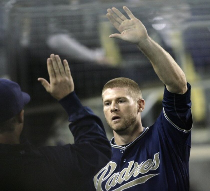 Chase Headley is greeted in the dugout by teammates after scoring on a sacrifice fly by Tony Gwynn against the Los Angeles Dodgers in the fourth inning