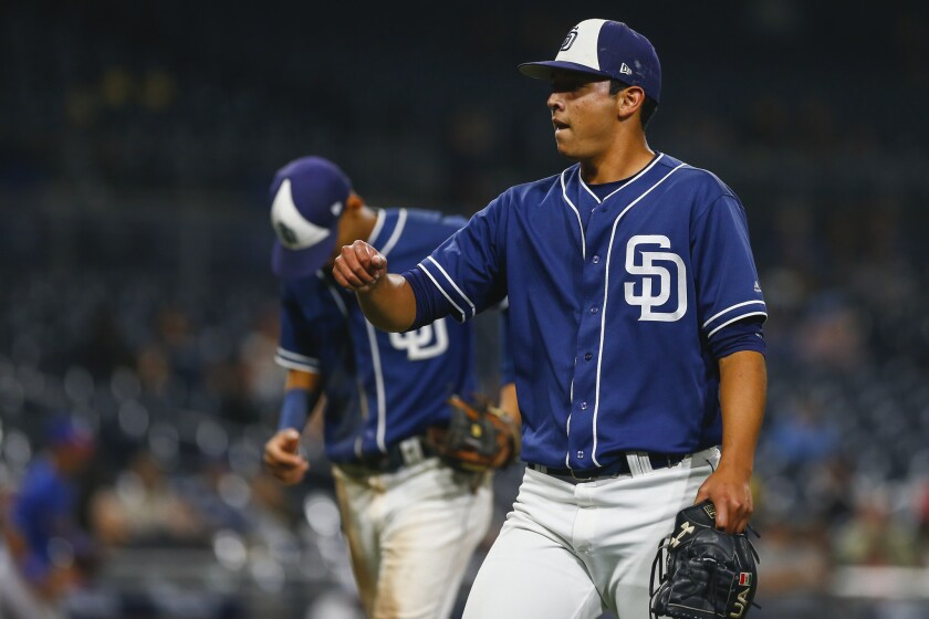 Padres reliever Andres Munoz walks off the field after a scoreless ninth inning against the Rangers.